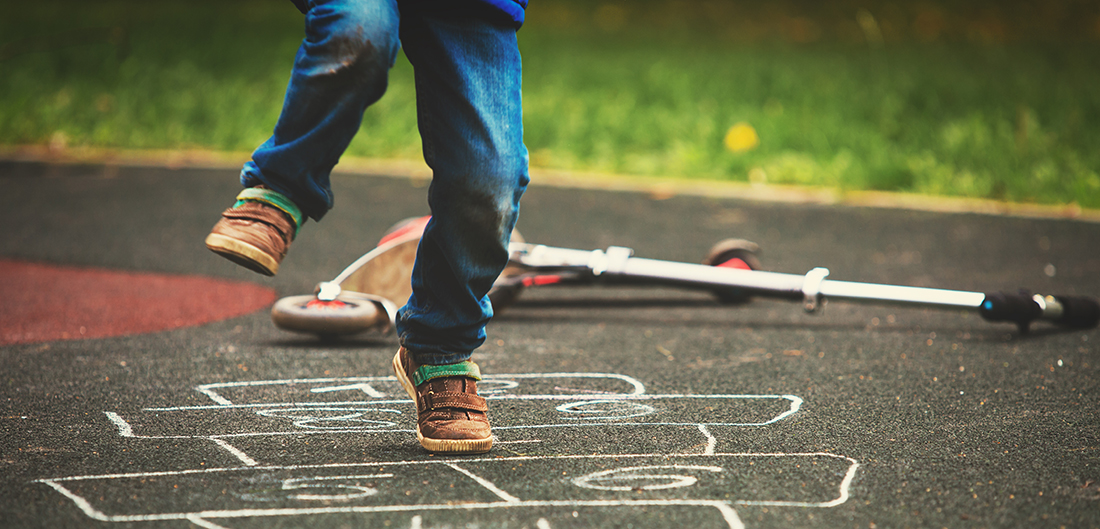 young boy hops on hopscotch drawing on driveway