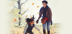 mother and daughter play in fall leaves