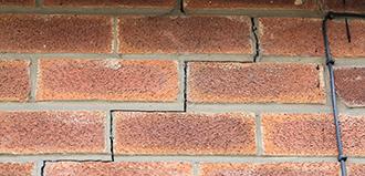 crack runs through mortar of brick wall, indicating foundation damage