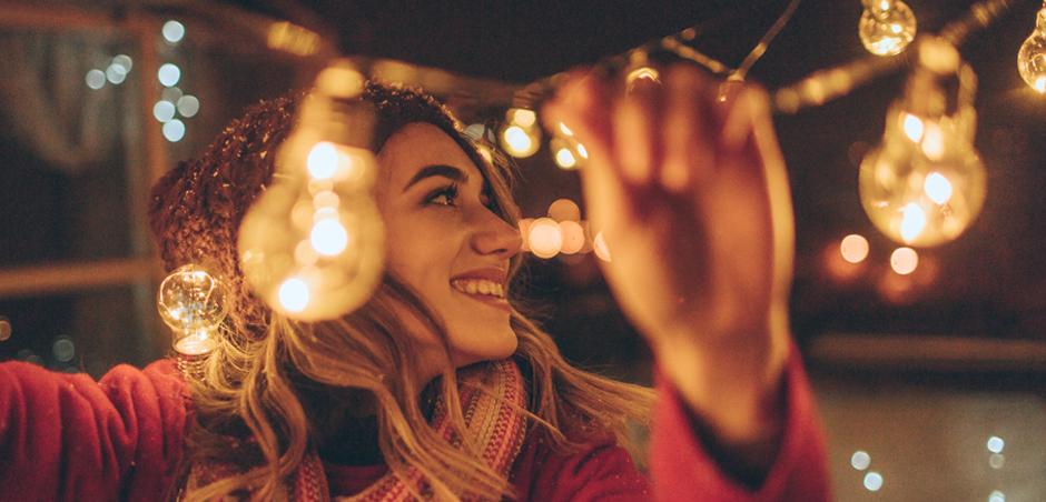 woman hangs string lights