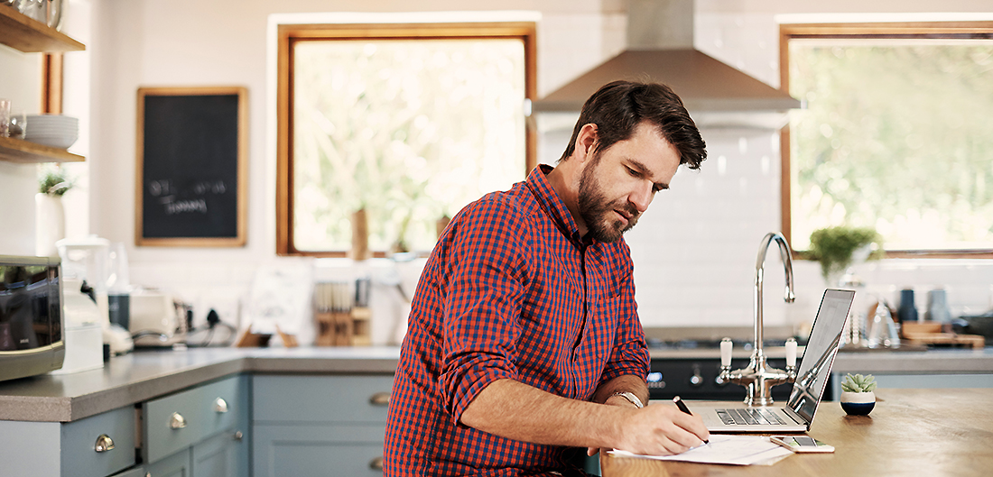 man writes on paper with laptop open in well furnished kitchen