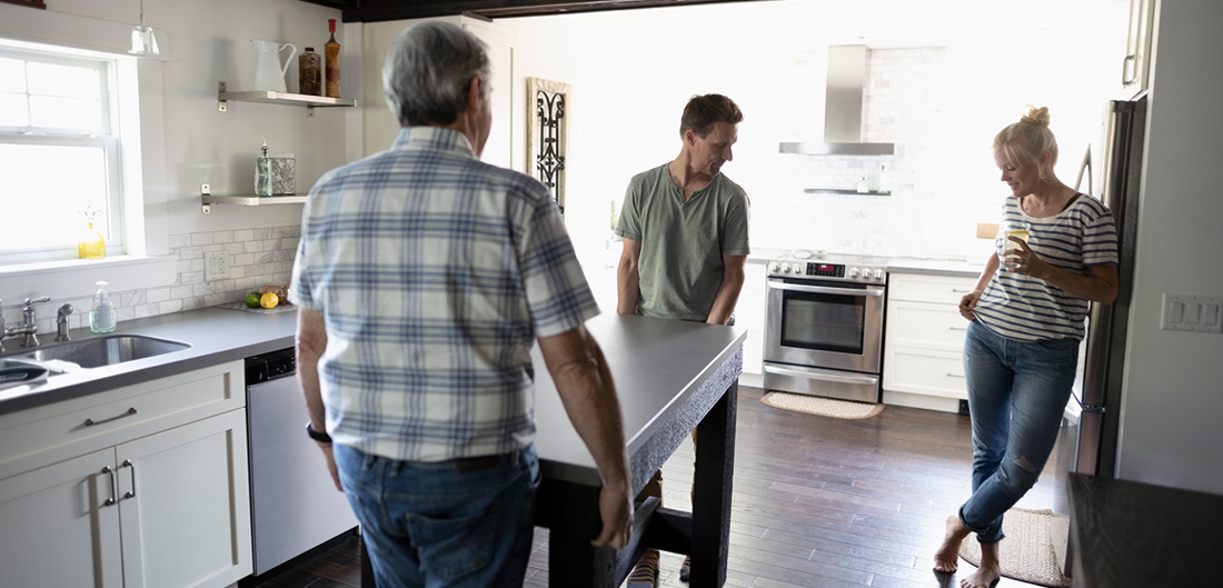 two men move stainless steel kitchen island while woman looks on