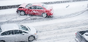 Car collides with barrier on snowy, icy road