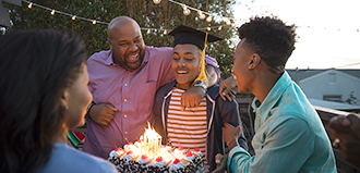 parents give cake to son celebrating high school graduation