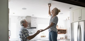 man and woman install light bulb in ceiling