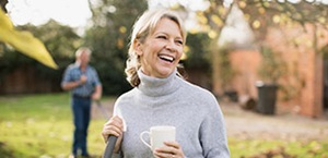 smiling senior woman holds coffee mug in yard