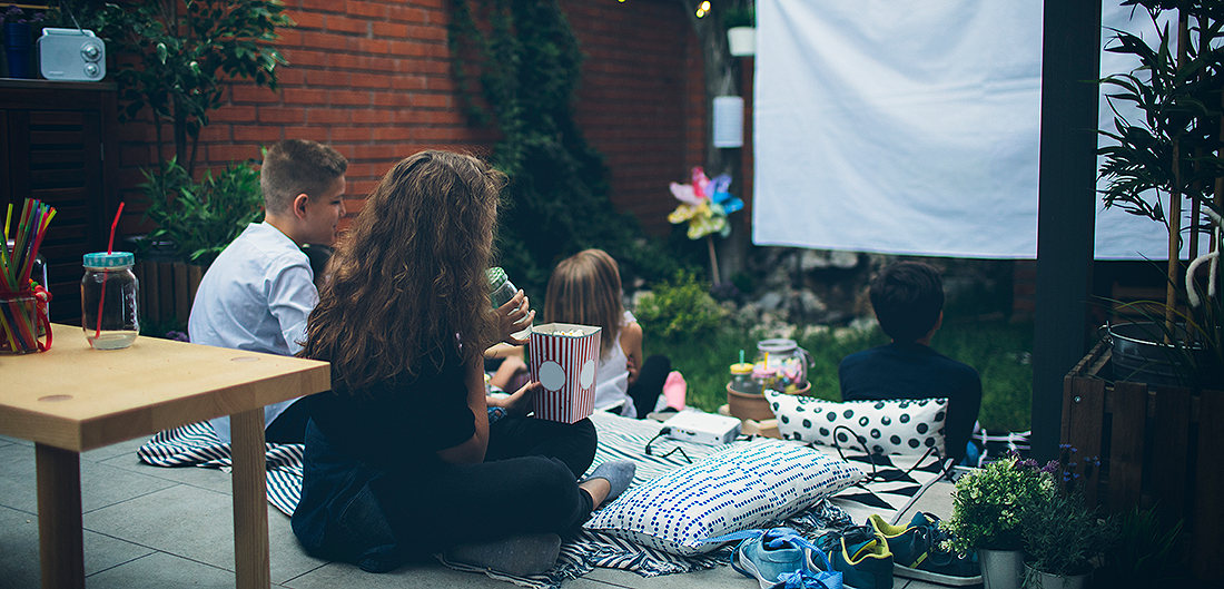 mother and three children eat popcorn and watch movie on outdoor screen