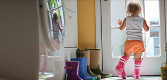 toddler in rain boots looks out back door of mudroom