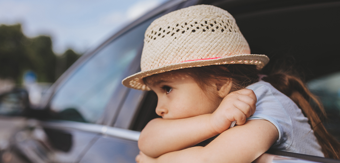young girl with straw hat looks forlorn with crossed arms outside car window