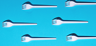 white plastic forks on blue background