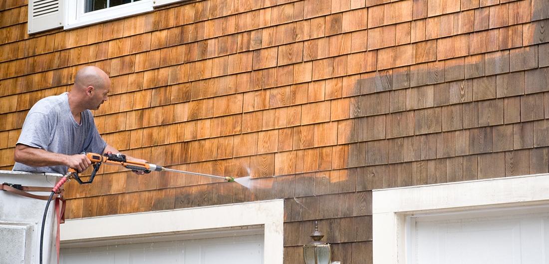 man power washes wood shake siding