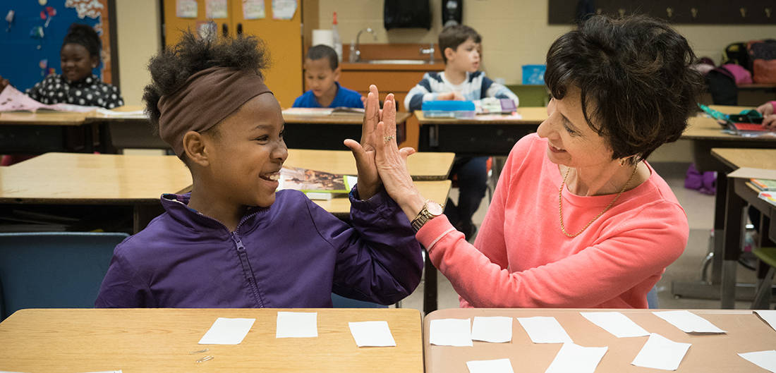 student and volunteer tutor high-five in classroom