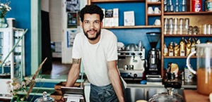 young male business owner stands behind counter of coffee shop
