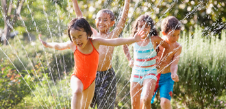 Children running through sprinkler
