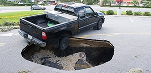 sinkhole opens in road beneath rear passenger's side tire of pickup truck