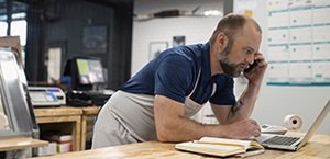 man in work apron leans over table to look at computer while talking on phone
