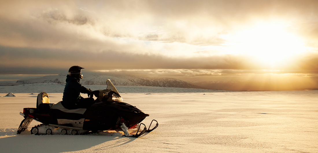 snomobiler rides on flat snow with sunset background