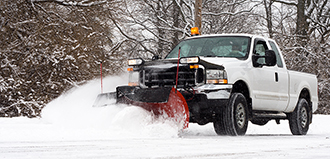 pickup truck with plow attached pushes snow off road