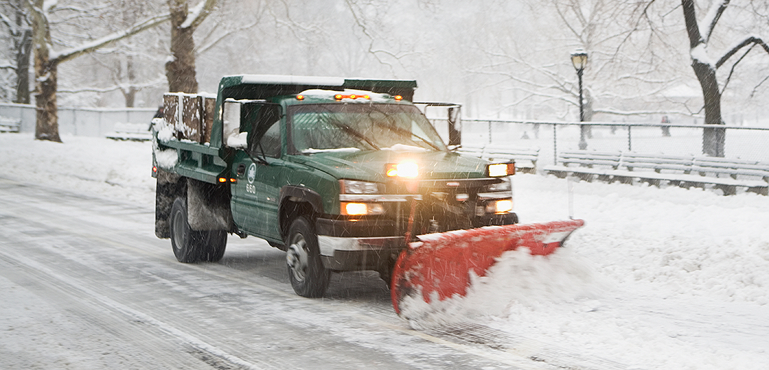 snowplow pushes snow off road