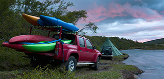 pickup truck with 5 kayaks is parked on a waterfront campsite with tent