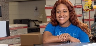 young woman smiles for portrait in Erie Insurance mailroom