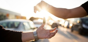hands exchange car keys in dealership lot