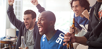 three young men cheer for football in living room