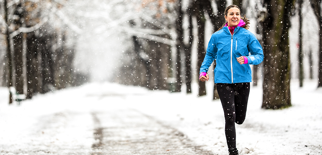 woman runs on snowy wooded path