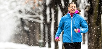 woman runs on snowy wooded path