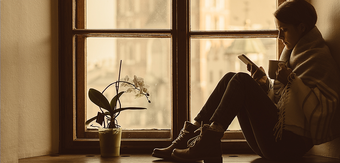 young woman reads book on chilly windowsill
