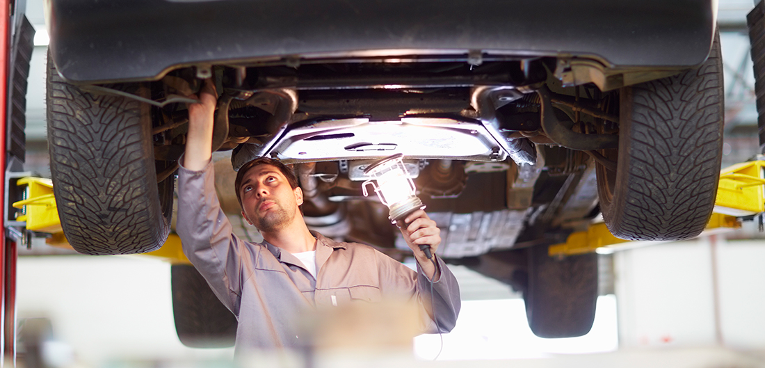 mechanic examines underside of car with light