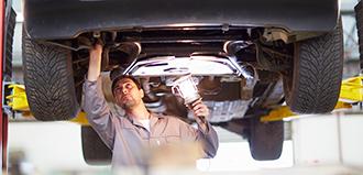 mechanic examines underside of car with light