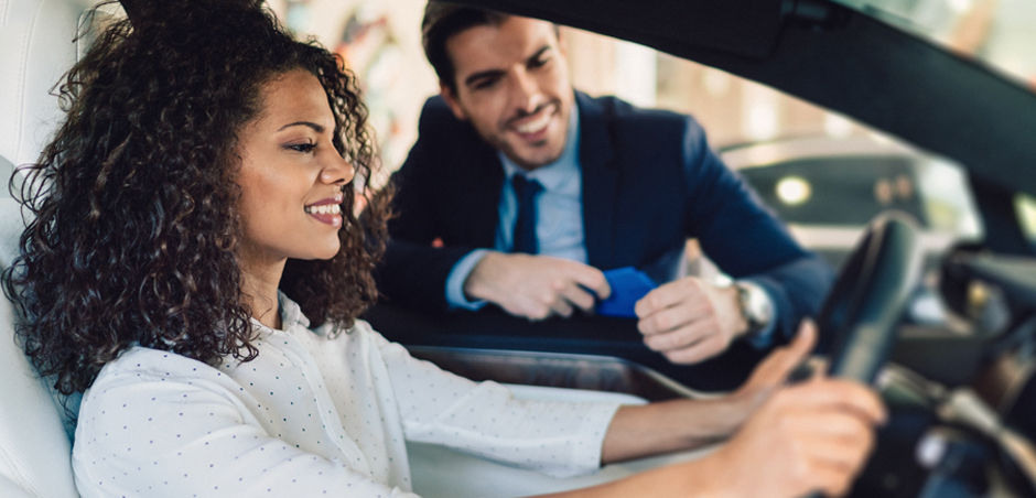 woman sits in driver's seat of new car with salesman in background