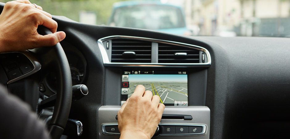driver uses built-in navigation system in car