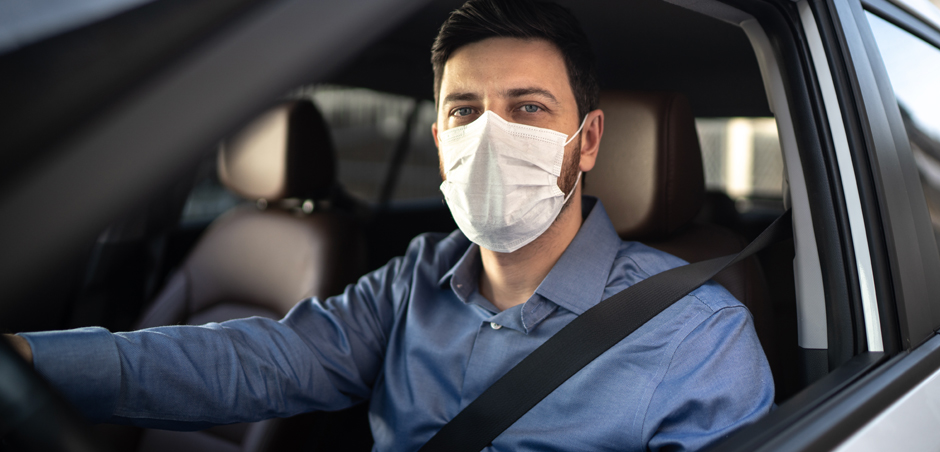 man wearing cloth face mask sits in driver's seat of car