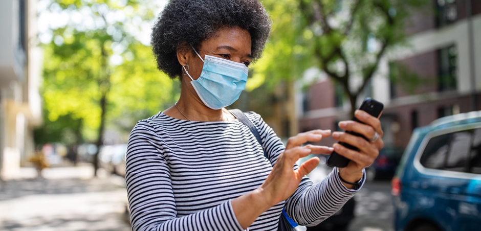 woman holds smartphone while wearing disposable mask