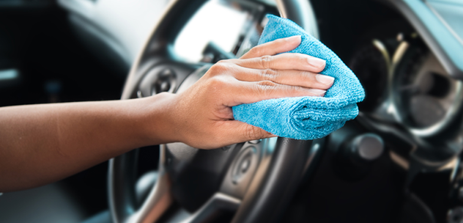 person's hand wipes steering wheel with cloth