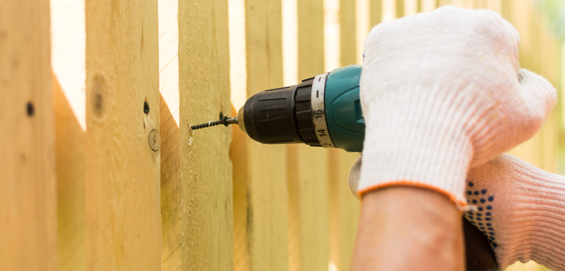 power drill on wooden fence