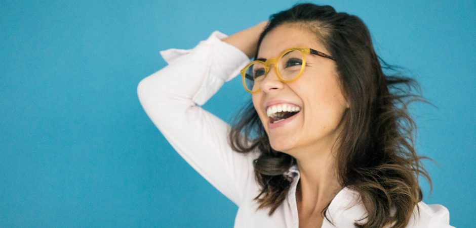 woman in glasses smiles