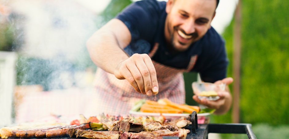 man in apron sprinkles seasoning on food on grill
