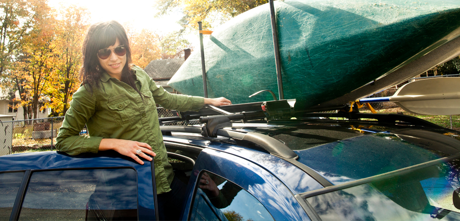 woman loads canoe on car