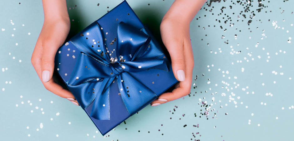 close up of hands holding small wrapped gift box on glittery background