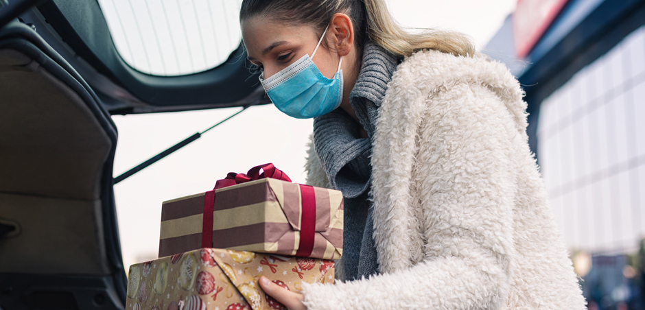 Woman wearing a mask and fuzzy winter jacket placing two wrapped presents in the trunk of her car.