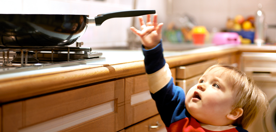 young child reaches for pan on stove
