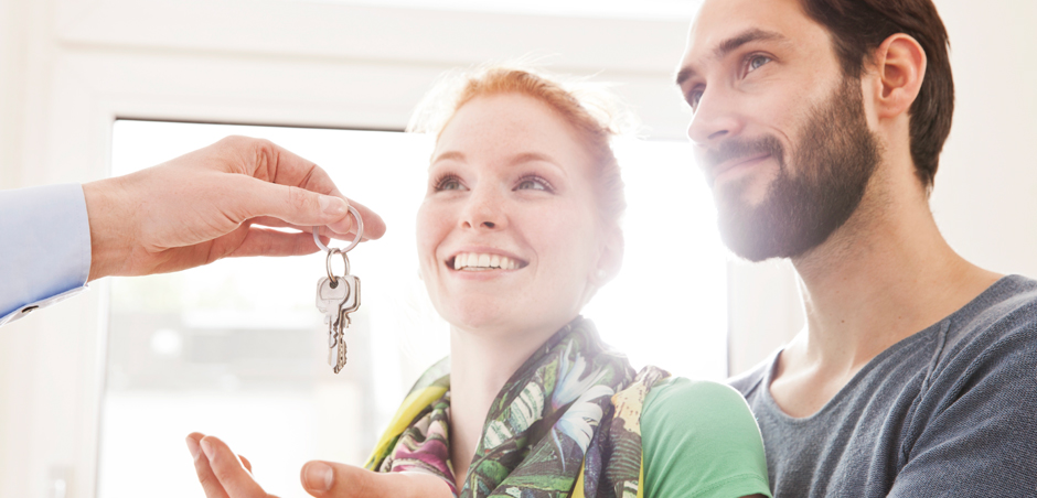 hand gives keys to young woman and man