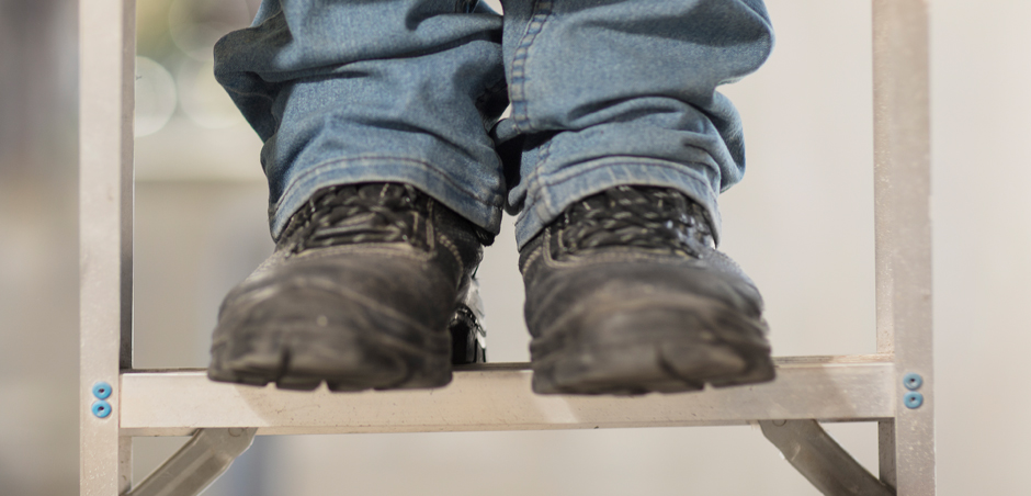 close-up of man's work boots on ladder