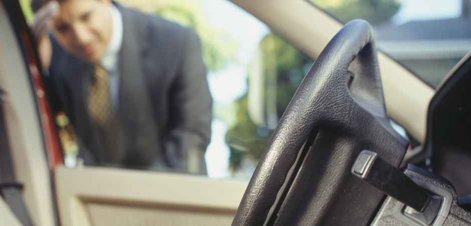 man looks in through driver's side car window