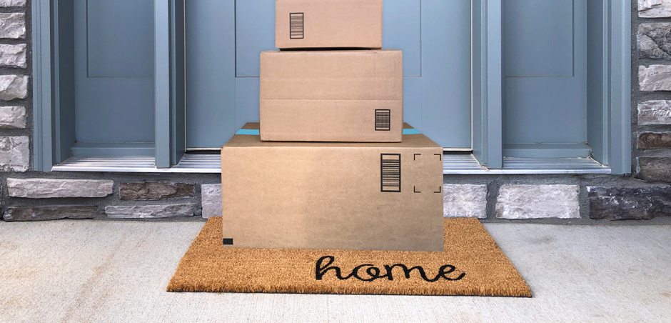 packaged stacked on a rug in front of a blue door on a home