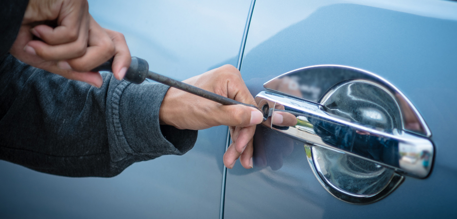 close-up of person's hands picking car door lock