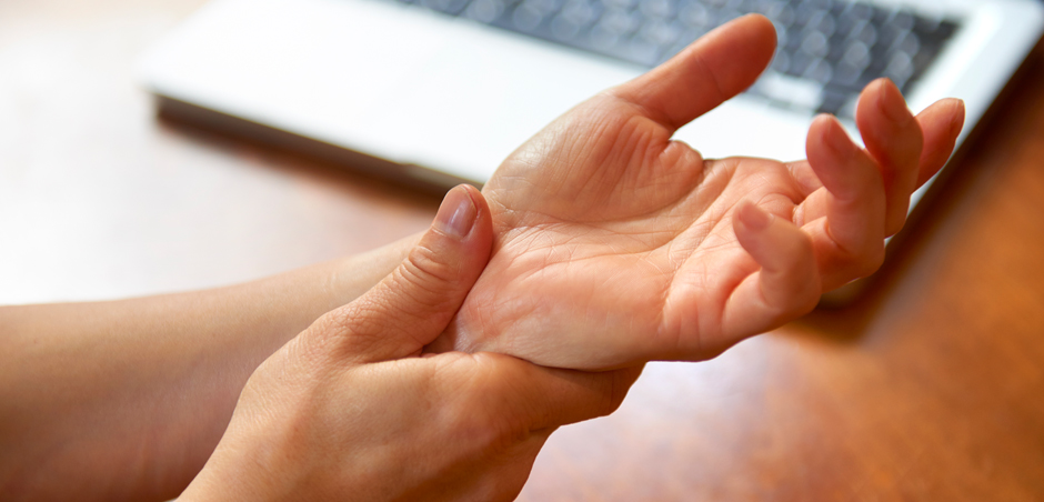 close up of thumb pressing wrist with laptop visible